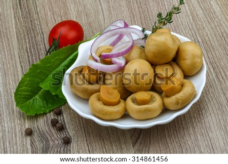 Pickled champignon with thyme on the wood background
