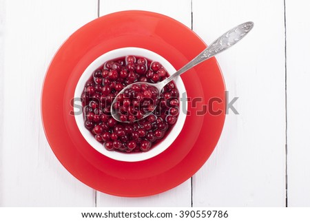 Pickled cranberries in a sweet syrup in a white bowl on a red plate and a white table. - stock photo