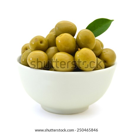 pickled green olives in a bowl and olive tree branch on a white background  - stock photo