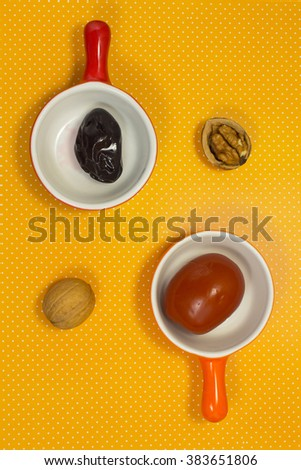 Pickled plums and tomatoes on a yellow background. Walnut. Still life - stock photo