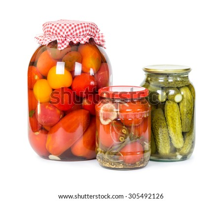 Pickled tomatoes and cucumbers in glass jars isolated on white background - stock photo