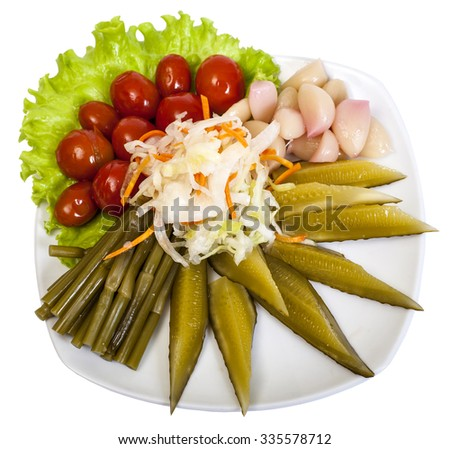 pickles: cucumbers, garlic, leek, tomatoes, cabbage and lettuce leaves in a plate on white background - stock photo