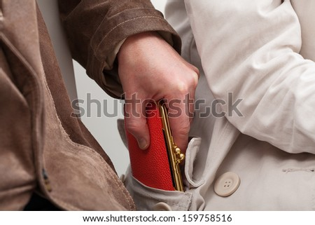 Pickpocket are stealing a woman's purse in the big crowd - stock photo