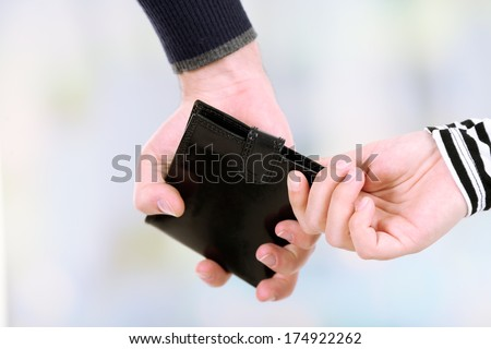 Pickpocket are stealing wallet,  close up, on light background - stock photo