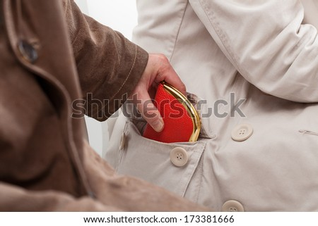Pickpocket stealing a wallet from a lady sitting next to him - stock photo