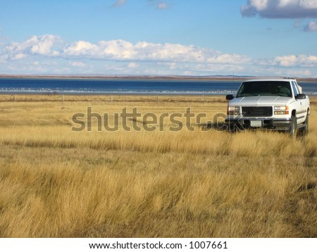 pickup out in the blowing prairie grasses of Saskatchewan - stock photo
