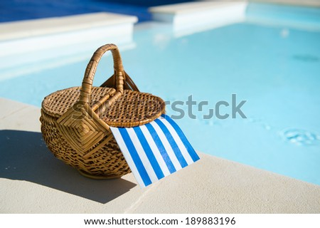 picnic basket at the swimming pool - stock photo