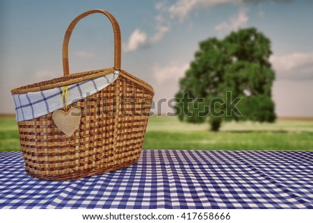 Picnic Basket Closeup On The Blue Checkered Tablecloth And Summer Toned Landscape With Alone Tree In The Field In The Background - stock photo