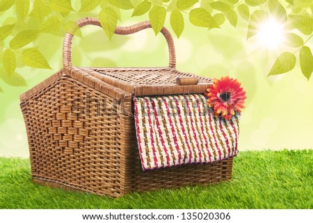 Picnic basket made of rattan shot in meadow over blue sky - stock photo