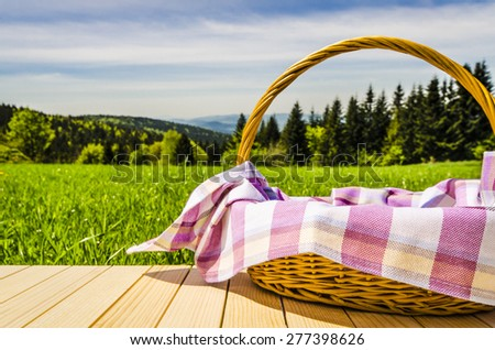 Picnic basket on wooden table - stock photo