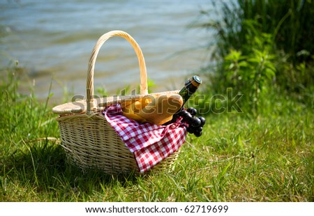 Picnic basket with food and cider bottle near the water - stock photo