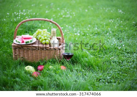 picnic basket with fruits and glass of wine on green grass in park