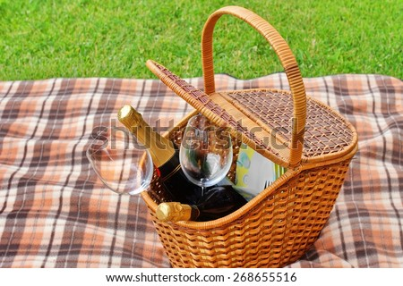 Picnic Basket With Plates, Food, Wine Bottles And Two Wineglasses  On The Blanket Close-up. Spring Lawn On The Background. Outdoor Picnic or Party or Scene. - stock photo