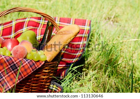 Picnic basket with red napkin fool of fruits, bread and wine with copy-space - stock photo