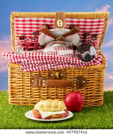 Picnic basket with sandwich and apple over grass, square image
