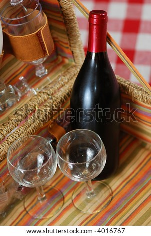 Picnic basket with wine and glasses on classic cloth