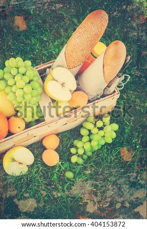 Picnic Basket Yellow Orange Green Fruits on Grass Background Summer Time - stock photo