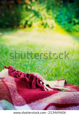 Picnic Cloth on Meadow in Summer, toned image with selective focus - stock photo
