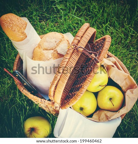 Picnic Food in a Wattled Basket on Green Grass, Fresh Bread, Apples. Image with filter effect instagram - stock photo
