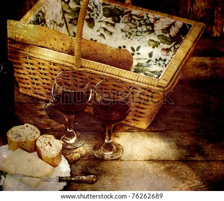 Picnic for two with wine, bread and cheese on a rustic background.  Heavily grunge textured. - stock photo