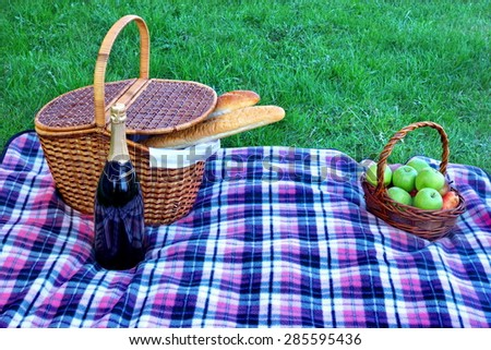 Picnic Hamper, Wicker Basket With Fruits, Champagne Wine Bottle on The Blanket Close-up. Green Park Lawn On The Background - stock photo