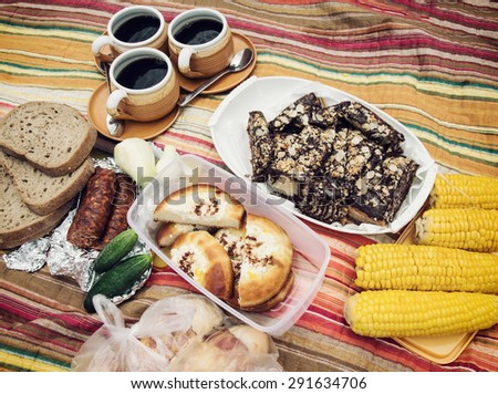 Picnic menu with deep dish pie with almonds and chocolate, curd cakes, bread, meat sausage, onion, corn and cups of coffee on the retro blanket. - stock photo