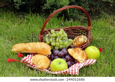 picnic on green grass with grapes,apples and croissants