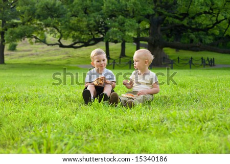Picnic on the grass. Two little boys have a dinner with pizza on the meadow at the noon - stock photo