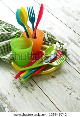 Picnic  plastic dishware and napkin on wooden boards - stock photo