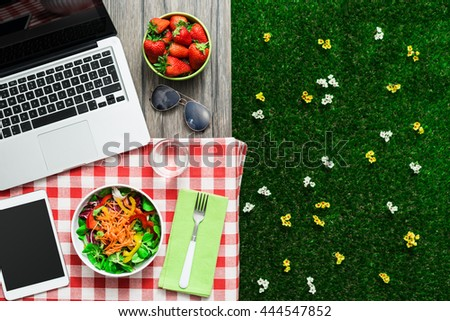 Picnic setting on a outdoor table with fresh salad bowl, laptop and tablet - stock photo