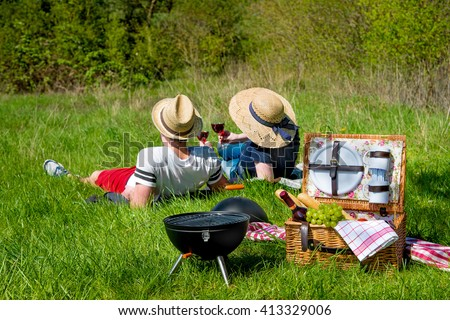 Picnic setting with red wine glasses, picnic hamper basket and burning fire in a portable barbecue - stock photo