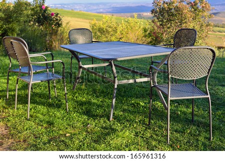 Picnic table and chairs on the lawn in courtyard of country house at morning time