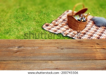 Picnic table, blanket and basket in the grass. Background, with space for text or image. - stock photo