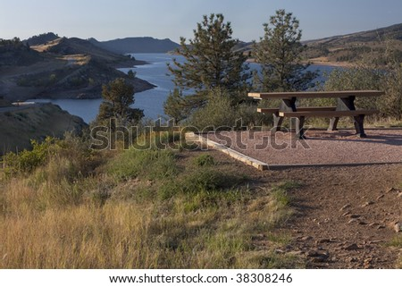 picnic table on shore of mountain lake (Horsetooth Reservoir) near Fort Collins, Colorado at foothills of Rocky Mountains, early morning, fall scenery - stock photo