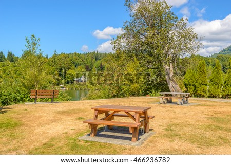 Picnic table over mountains and blue sky.