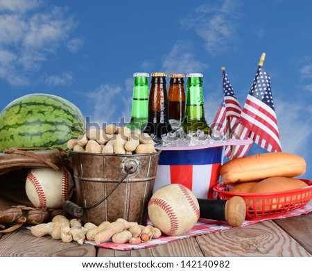 Picnic table ready for a Fourth of July celebration. Cold beer in an Uncle Sam Hat, watermelon peanuts, baseball, and hot dog buns fill the table, with a blue cloudy sky background. - stock photo