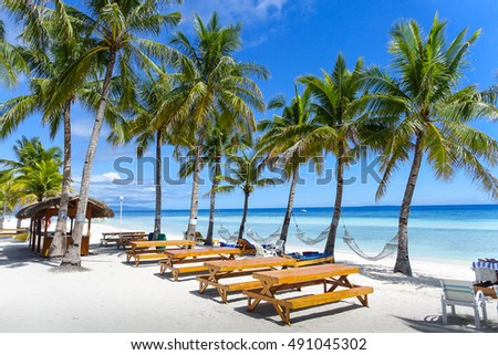 Picnic tables and hammocks lining a beautiful beach