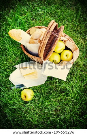 Picnic Wattled Basket with Fresh Bread, Apples and  cheese on Green Grass - stock photo