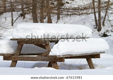 Picnic wooden table after a big snowfall - stock photo