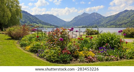 pictorial seafront of schliersee lake, flower beds and bavarian alps - stock photo