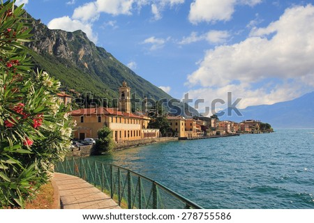 pictorial village gargnano, lago di garda, lakeside promenade with oleander and church - stock photo