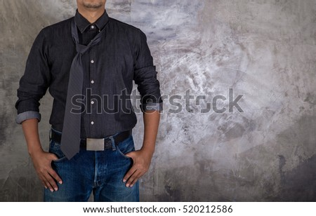 Picture a young man dressed in jeans and wearing denim cloth shirt with a tie.
