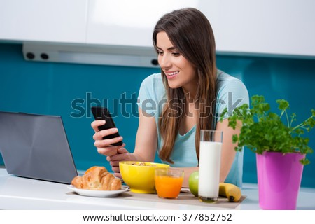 Picture a young woman eating breakfast and taking a phone call, sitting at the kitchen table.