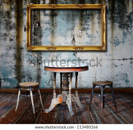 Picture frame and furniture in grunge room. - stock photo