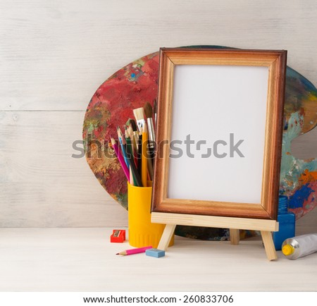 picture frame and paints on wooden background - stock photo