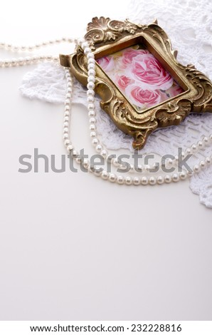 picture frame and pearl necklace on white The picture in the frame is my work. - stock photo