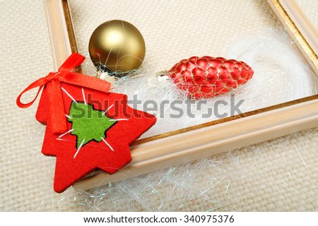 picture frame decorated with Christmas toys close-up on beige wool fabric background   - stock photo