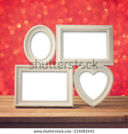 Picture frame on wooden table over bokeh background - stock photo