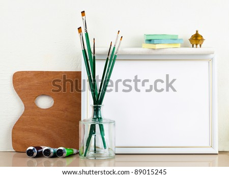 Picture frame with a palette and paintbrushes - stock photo