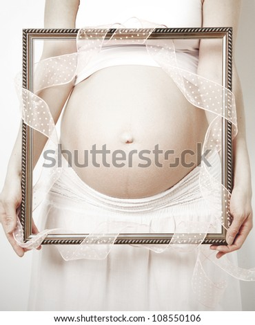 Picture framed pregnant belly and a ribbon, processed in sepia tone - stock photo